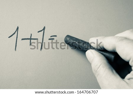 Hand writing simple mathematics  equation with chalk - stock photo