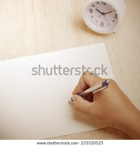 Hand writing something on the paper sheet - stock photo