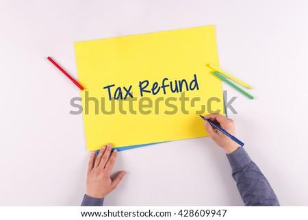 Hand writing Tax Refund on yellow paper - stock photo