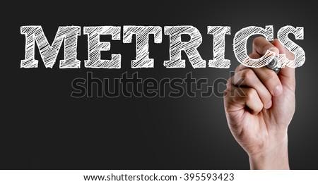 Hand writing the text: Metrics - stock photo