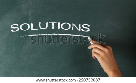 Hand writing the word Solutions on a blackboard - stock photo