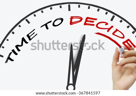 Hand writing time to decide concept with red marker on transparent wipe board. - stock photo