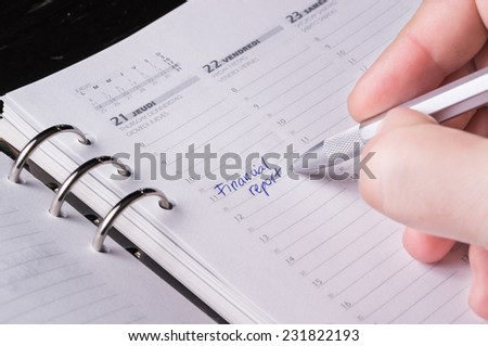 hand writing with silver pen on open business agenda - stock photo