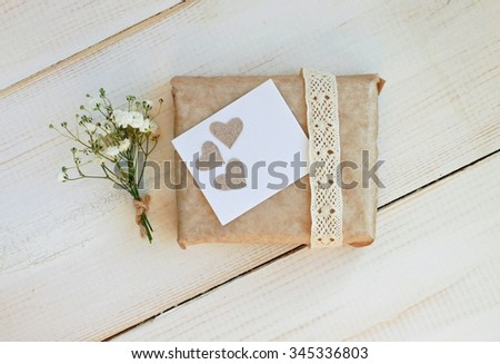 Handcrafted gift box wrapped in parchment paper, decorated lace ribbon, paper hearts, tender gypsophila flowers - stock photo