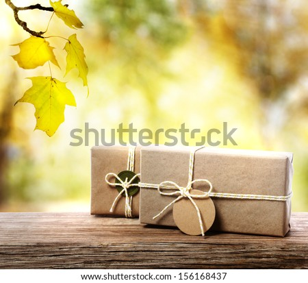 Handcrafted gift boxes on aged  wooden boards with an autumn foliage background - stock photo