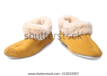 Handcrafted leather slippers with wool lining on white background - stock photo