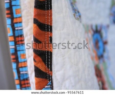 Handcrafted quilt of cotton fabric with machine stitched quilting for warmth and comfort. - stock photo