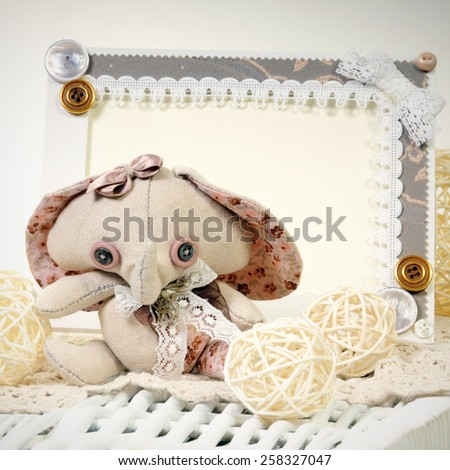 handcrafted soft toy vintage style elephant with enormous ears on the handmade pink frame decorated with buttons background - stock photo