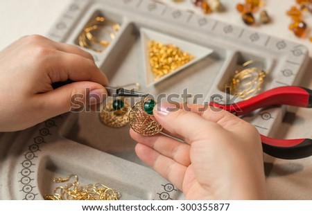 handcrafting a pair of beautiful bijouterie earrings - stock photo