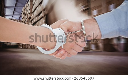 Handcuffed business people shaking hands against worker with fork pallet truck stacker in warehouse - stock photo