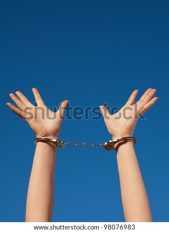 Handcuffed woman's hands against blue sky - stock photo