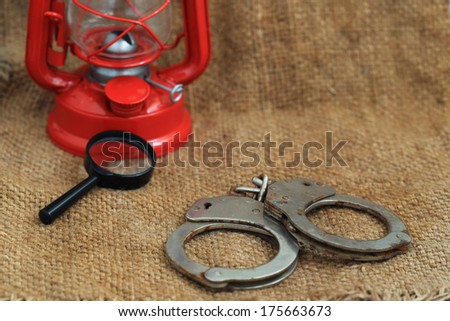 Handcuffs and Detective glasses - stock photo