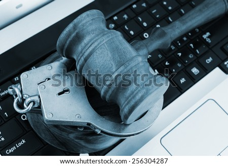Handcuffs and gavel on laptop - stock photo