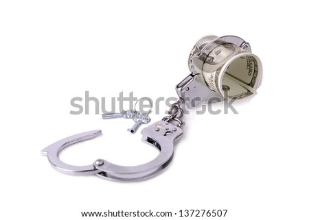 handcuffs around a roll of 100 dollar bills, concept of money tied up in something - stock photo