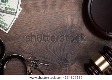 handcuffs gavel and money on the wooden background - stock photo