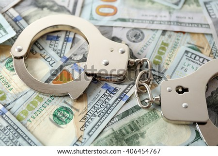 Handcuffs on dollar banknotes. Corruption concept - stock photo