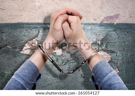 Handcuffs on Hands on the Old Wall Background closeup - stock photo