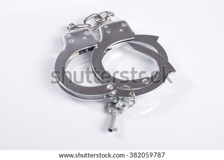 Handcuffs with a key on white background - stock photo