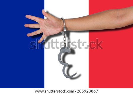 handcuffs with hand on France flag - stock photo