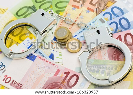 Handcuffs with money in background - stock photo