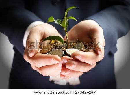 Handful of coins with growing sprout on white background - stock photo
