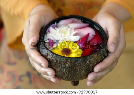 Handful of spa flowers in coconut shell. - stock photo