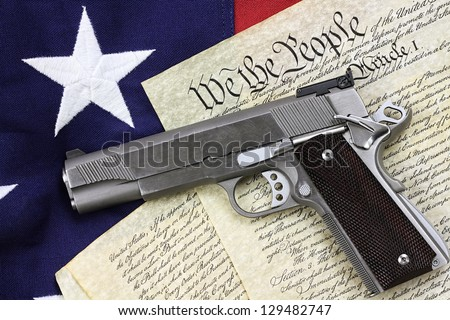 Handgun lying over a copy of the United States constitution and the American flag. - stock photo