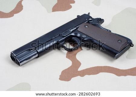 handgun on camouflage uniform - stock photo