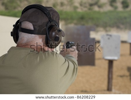 Handgun shooter readying to shoot at steel targets - stock photo