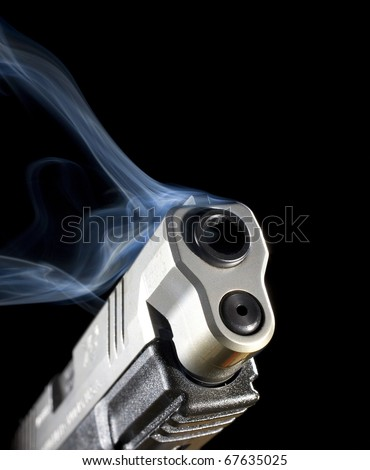 Handgun that is pouring out blue smoke after a shot was taken - stock photo