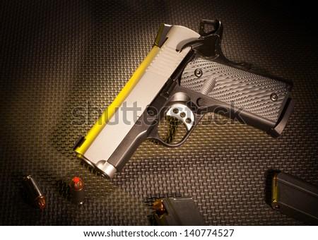 Handgun with ammunition on a dark textured background - stock photo