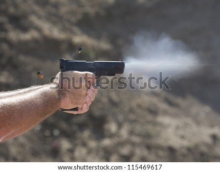 Handgun with empty brass in the air and the bullets vapor trail visible - stock photo