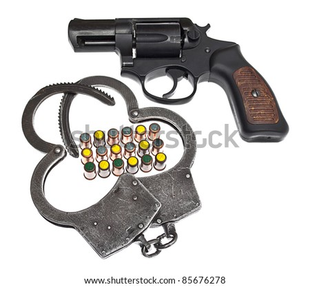 Handgun with handcuffs and bullets isolated on white - stock photo