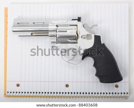 Handgun with school notebook paper. - stock photo