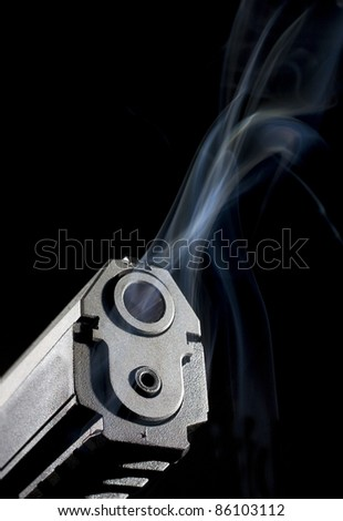 Handgun with smoke coming from its hot barrel - stock photo