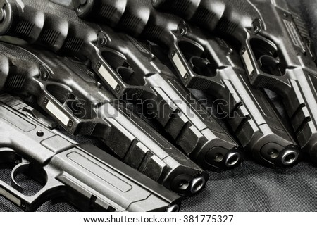 handguns in a row on the black background - stock photo
