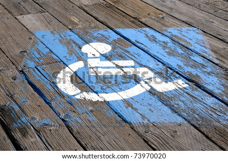 Handicap parking sign on the planks of the Santa Monica Pier in Southern California - stock photo