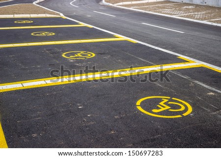 Handicap parking space just painted. Universal wheelchair symbols painted on the asphalt. Focus is on the at the first sign of wheelchair symbols.  - stock photo