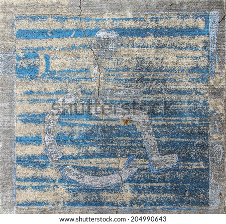 handicap wheelchair man symbol imprinted on a grungy pebble pavement - stock photo