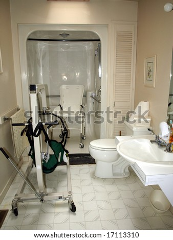 Handicapped bathroom with shower chair, lift, and specially designed sink for a wheelchair - stock photo