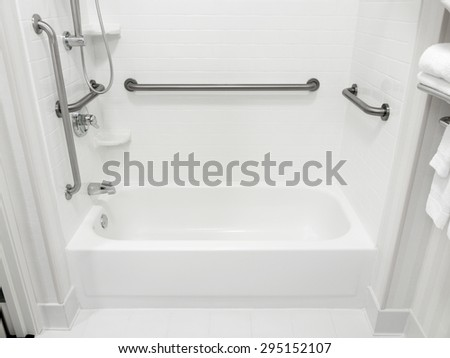 Handicapped disabled access bathroom bathtub with grab bars - stock photo