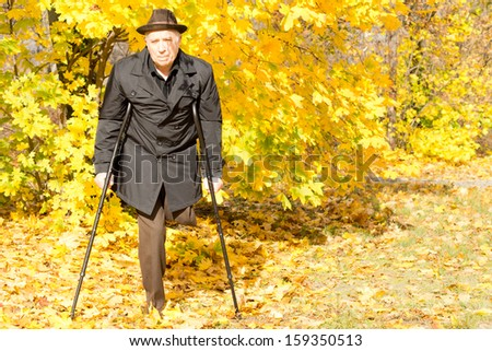 Handicapped elderly male amputee in a fall park taking a walk on his crutches surrounded by colourful yellow autumn leaves - stock photo