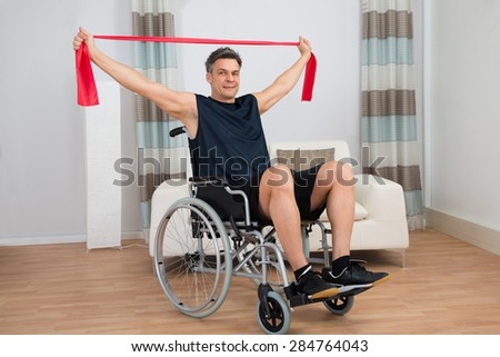 Handicapped Man On Wheelchair Exercising With Resistance Band At Home - stock photo