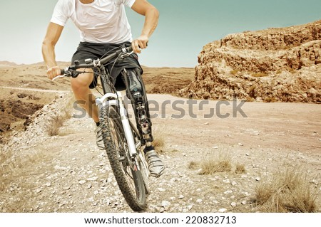 Handicapped mountain bike rider rides in a barren landscape  - stock photo