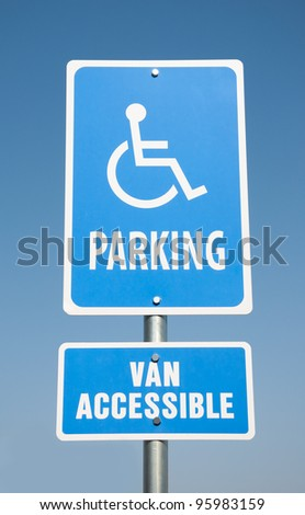 Handicapped parking sign against clear blue sky - stock photo