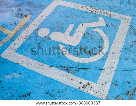 Handicapped parking sign on the road is quite old. - stock photo