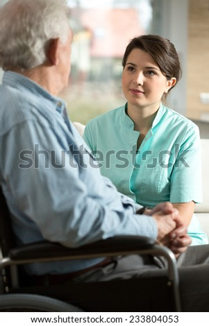 Handicapped senior man and his smiling nurse - stock photo