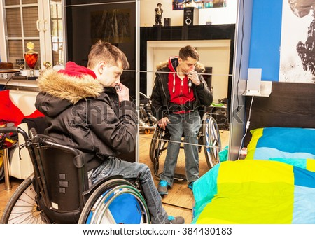 Handicapped teenager shaved in front of a mirror cabinet - stock photo
