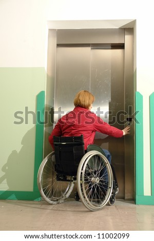 Handicapped woman on wheelchair using lift in building - stock photo