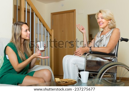 Handicapped woman talking with female guest at the table. Focus on mature - stock photo